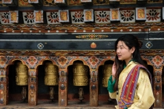 Bhutanese young woman wearing a kira (national dress) standing in front of prayer wheels in monastery