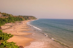 Beautiful and relaxing beach flanked by green palm trees at sunset. Varkala, Kerala, India.